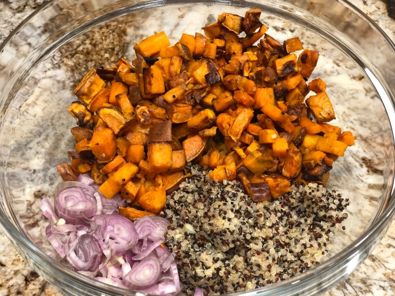 Glass bowl of orange sweet potato chunks, pink shallot slices and brown and tan quinoa