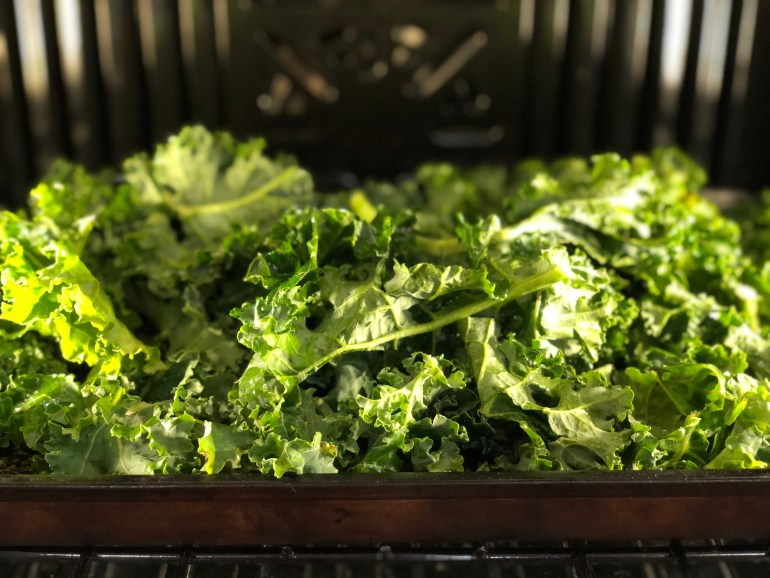 Green curly leaves on a baking pan