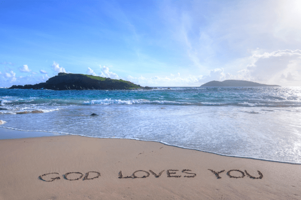 """A beach with the words """"God Loves You"""" written in the sand."""