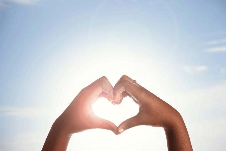 2 hands making a heart shape against a blue sky