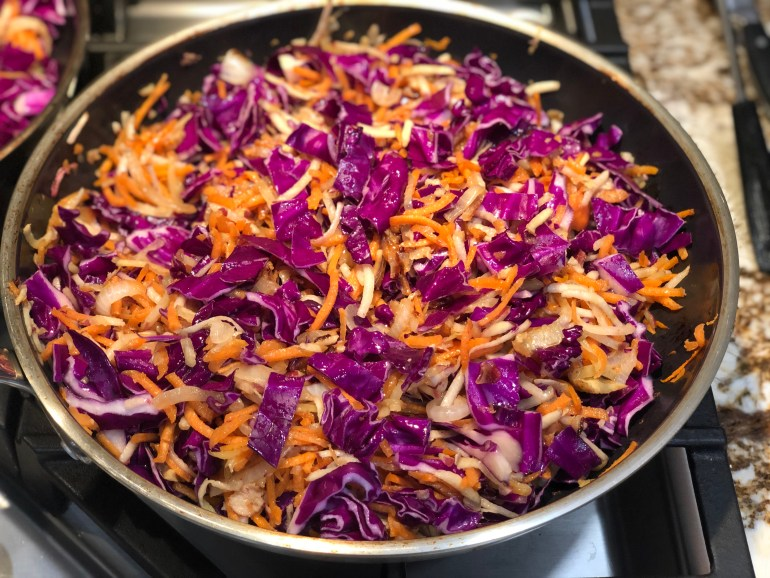 Shredded purple cabbage, carrots, potatoes in a saute pan