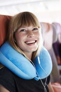 Young female airplane passenger with headphones smiling while wearing a travel pillow and sitting up straight