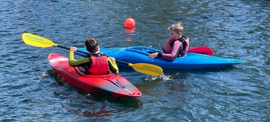 two children learning to canoe