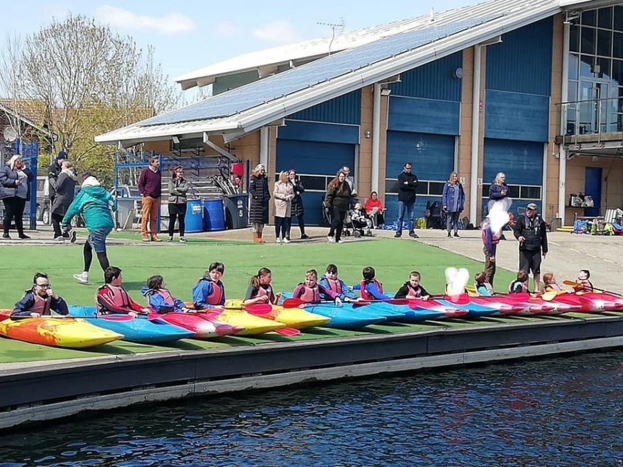 children in canoes receiving instructions before going in the water