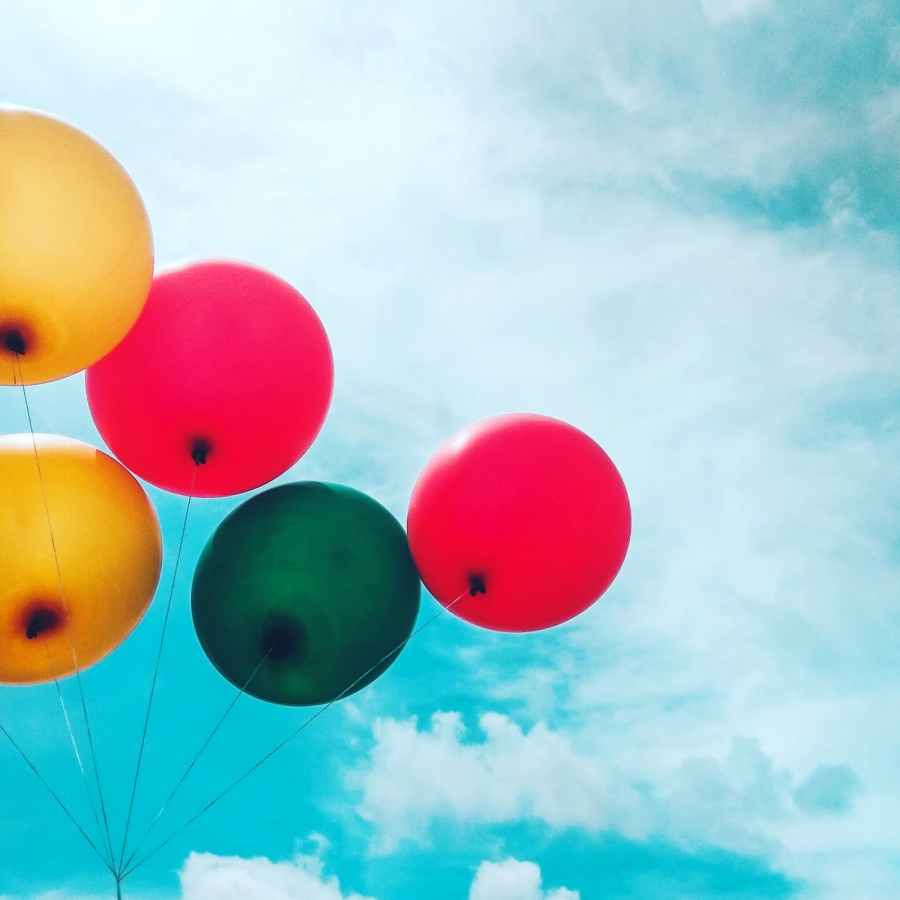brightly coloured balloons against cloudy sky