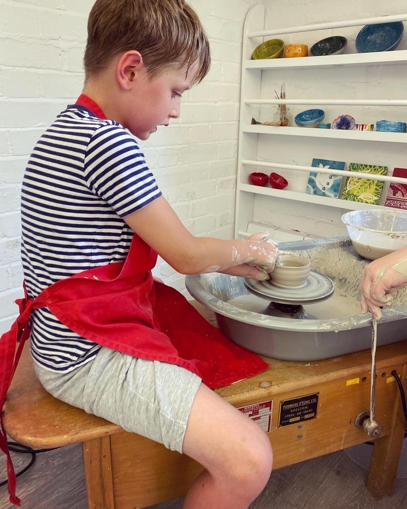 Boy sat at a pottery wheel making a pot