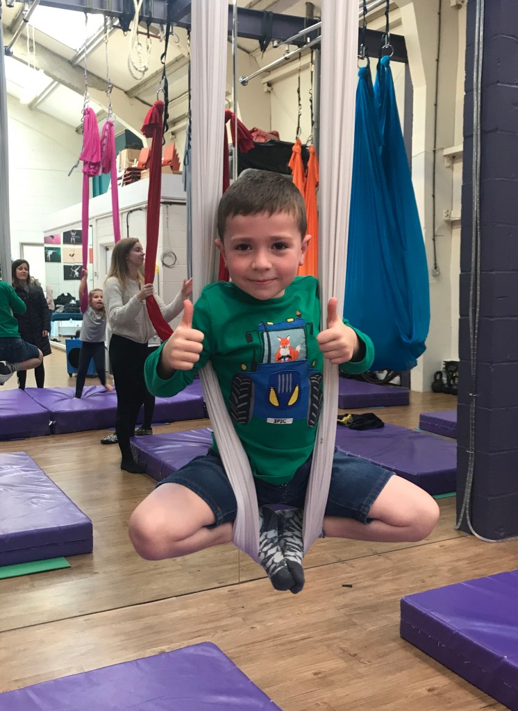 Boy with thumbs up on a material yoga swing