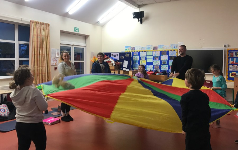 Children playing with a colourful parachute