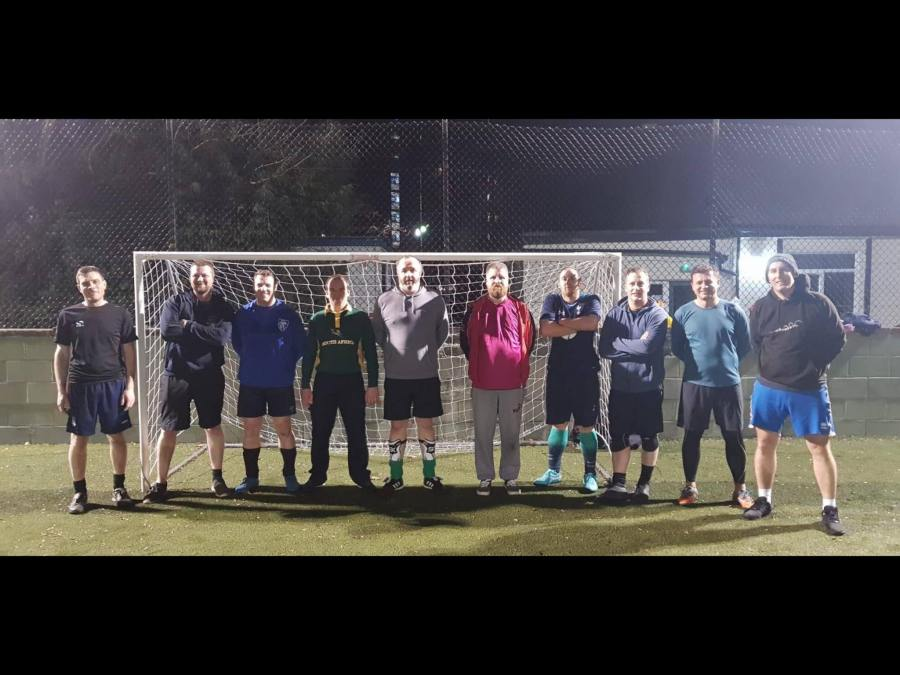 a row of footballers stood in front of a goal