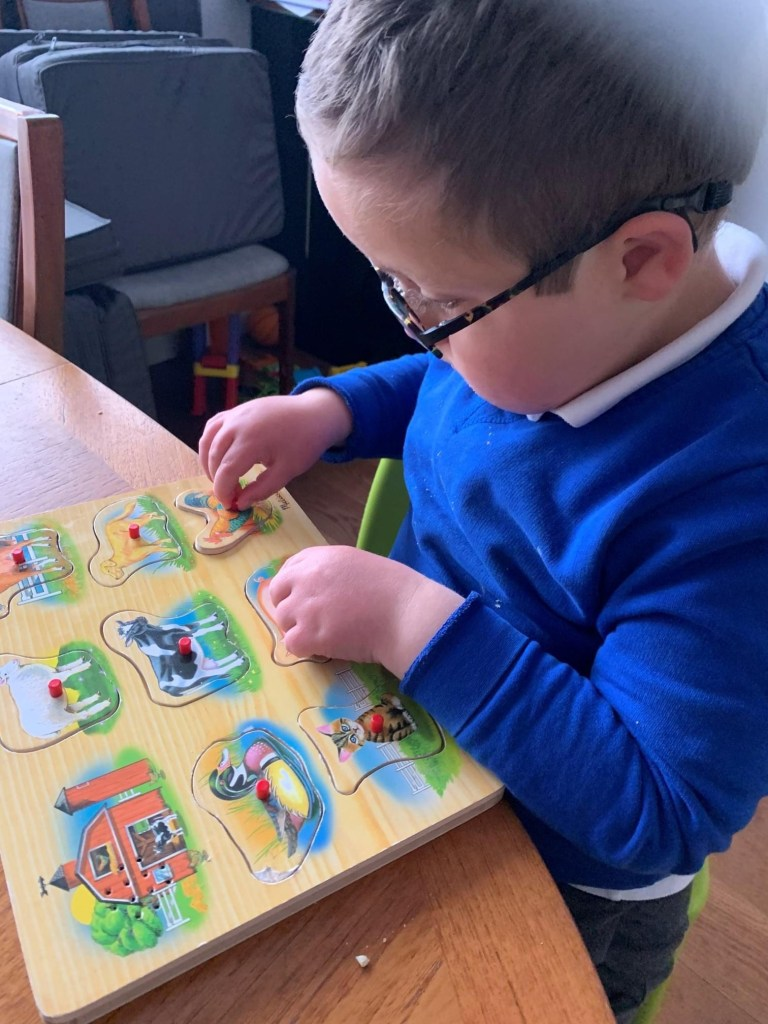 Boy playing with a chunky wooden peg puzzle