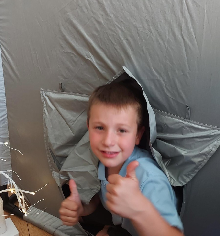 Boy peeping out of a giant black out tent with his thumbs up