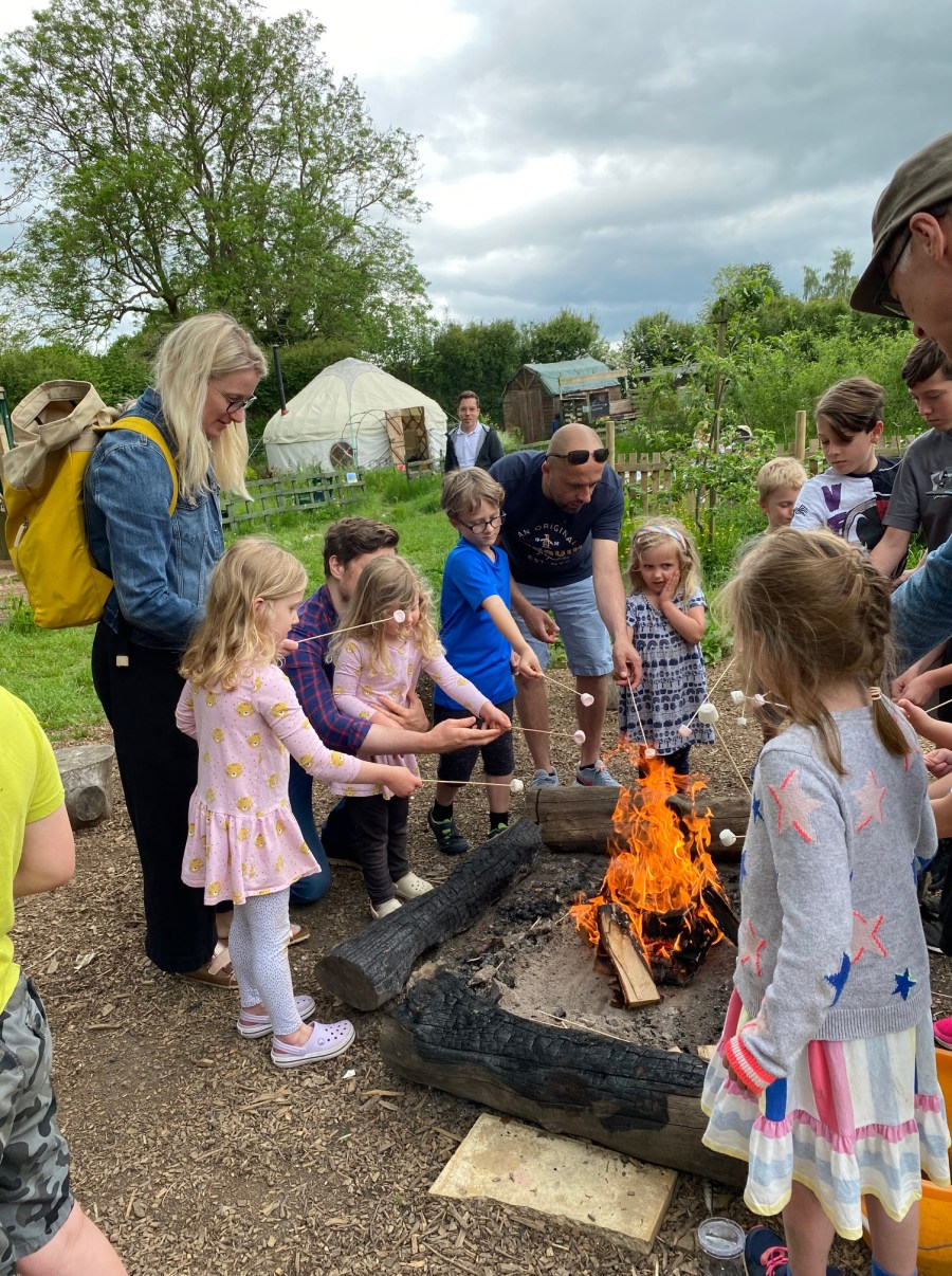 Children, young people and their families toasting marshmallows around a campfire at The Patch for SPACE Hertfordshire's exclusive session