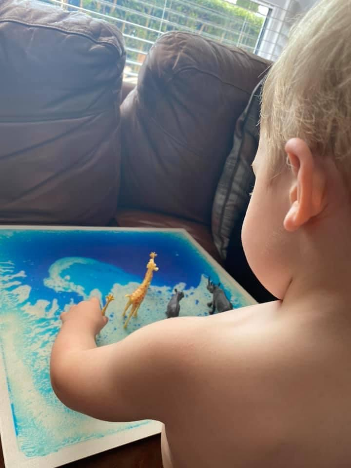 Child playing with toys animals on sensory tile from Lending SPACE