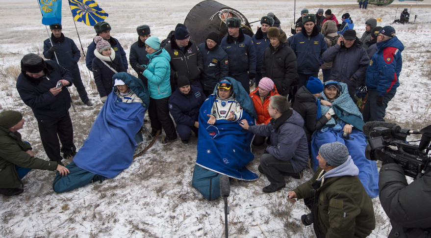 Expedition 41 flight Engineer Alexander Gerst of the European Space Agency, left, Commander Max Suraev of the Russian Federal Space Agency (Roscosmos), center, and NASA Flight Engineer Reid Wiseman, sit in chairs outside the Soyuz TMA-13M capsule just minutes after they landed in a remote area near the town of Arkalyk, Kazakhstan, on  Nov. 10, 2014. Credit: NASA/Bill Ingalls