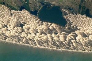 Aerial view of crescent-shaped sandy dunes running along the extent of the greeny-blue Atlantic coastline of Brazil.