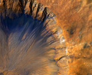 Aerial view of an impact crater on mars depicted in false colour to highlight steep scree slopes in blue and crater edges in orange.