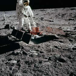 Astronaut using a seismometer to detect ground vibrations on the moon for the first time.
