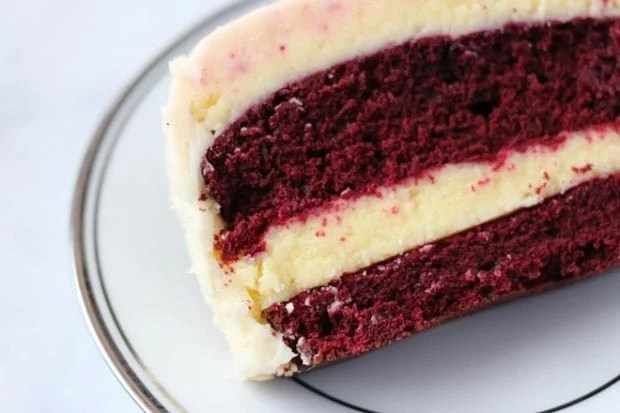 A beautiful red velvet cheese cake sits on a white plate. Delicious.