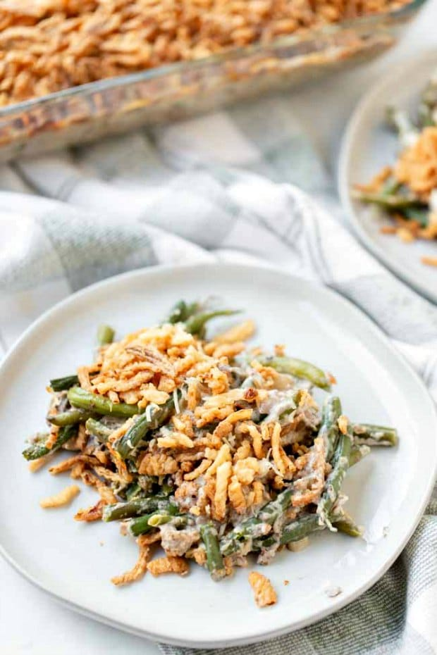 plate full of green bean casserole in front of casserole dish