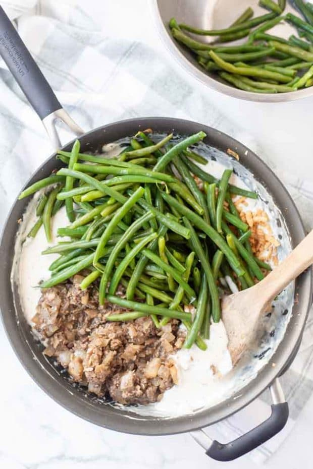 Skillet with ingredients for green bean casserole
