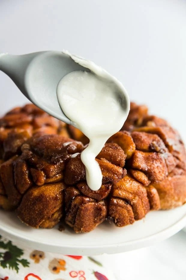 frosting being dripped from spoon onto monkey bread