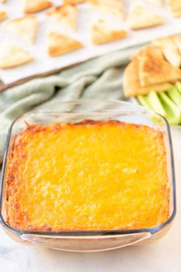 casserole dish with buffalo chicken dip in it placed in front of pita chips