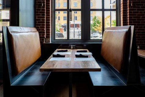 """SPACE designed and fabricated the booth seating with leather """"saddle"""" cushions."""
