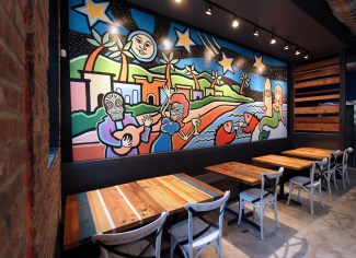 Craig Downs' mural, surrounded by SPACE designed- and built-tables. Notice how the pattern of the wood tabletops carries up the wall on the far side of the mural. #totallyplannedthat