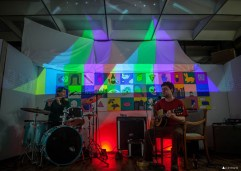 Local band performs during Art Walk at 1120 Creative House. The kaleidoscopic video projections by Kris Crews enhanced sensory experiences. The large grid of paintings are by Angela Larsen. Photo by Kris Crews.