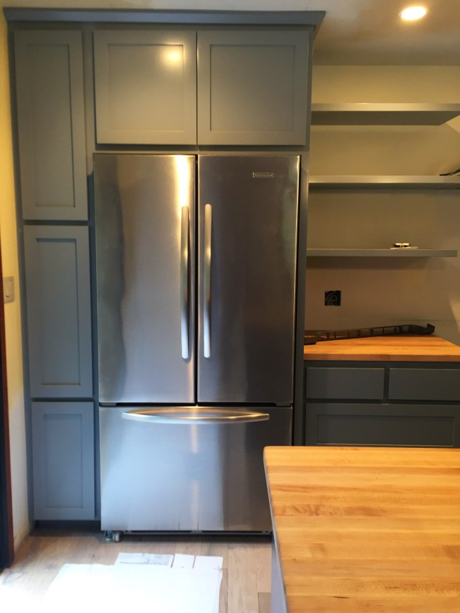 Sweatshirt grey cabinets and stainless steel fridge