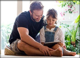 Photo of father reading to his daughter (for personal lines insurance)