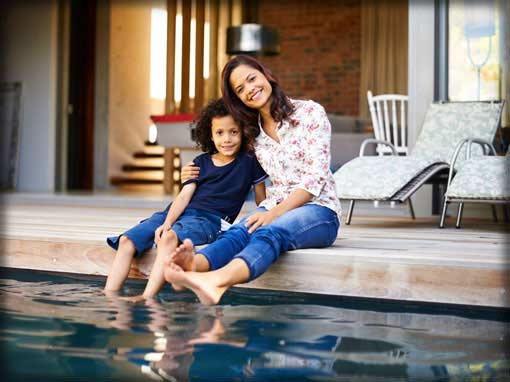 Personal lines insurance photo showing mother and child sitting by their pool