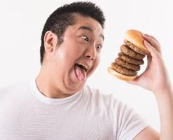 ハンバーガーを食べようとする太った男性