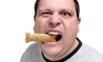 A man chews on a dog bone.