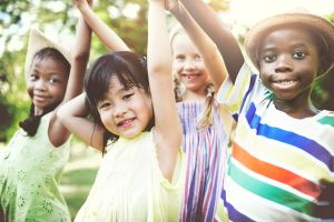 group of multicultural, smiling children with their arms raised