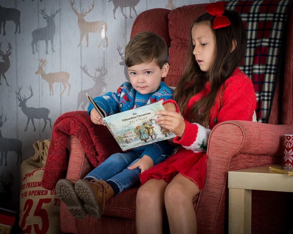dos niños leyendo un libro de navidad
