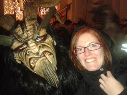 Yo posando con un Krampus. Mi cara refleja la expresión que adopté durante todo el tiempo que duró el desfile, para intentar evitar que se acercaran a mí y me pegaran.