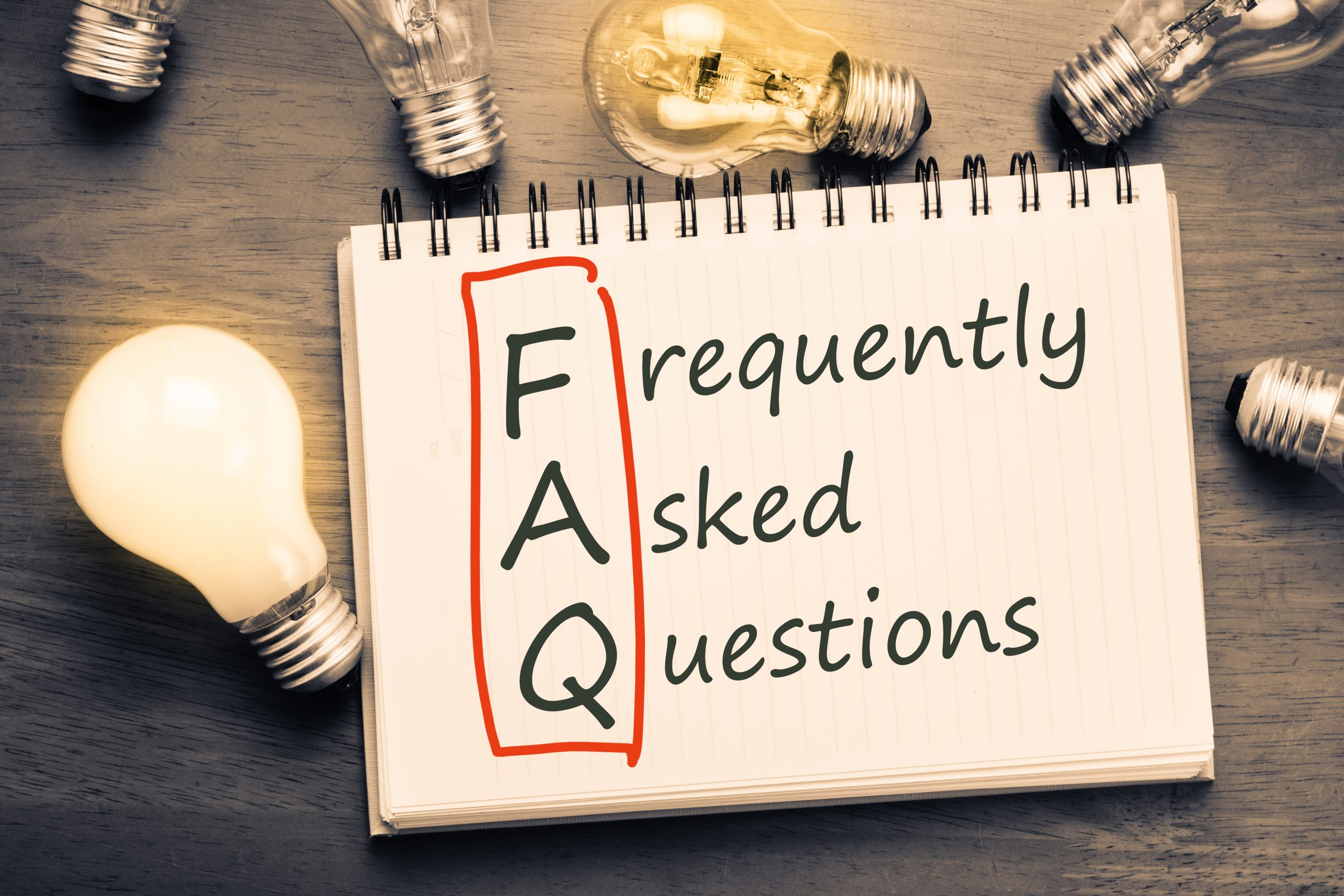 "Notepad with first letters of text ""Frequently Asked Questions"" circled in red to form the abbreviation ""FAQ"""