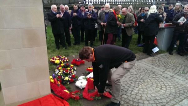 """Allan legt Blumen am Denkmal nieder. Er tut dies für die Ernst Thaelmann-Gedenkstätten in Berlin und Hamburg. Der Text auf dem Band """"DANKE BRÜDER"""" zeigt die unerschütterliche Solidarität der internationalen Arbeiterklasse."""
