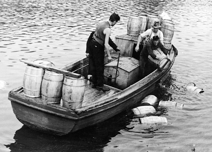 The German steamer, S/S Heyer, operating a regular food shipping service between Odense and Hamburg, was sabotaged in the Odense Havn ('Port of Odense') 31 August 1944. The cargo of butter, seed and condensed milk was scattered in the port basin. In the photo the men are recovering casks of butter