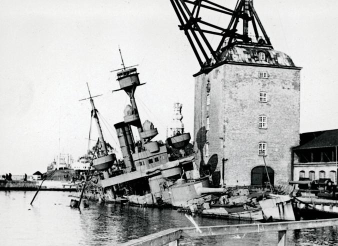 Besættelsen og befrielsen: 12. Skibssabotagen: Krydseren Peder Skram minesprængt så grundigt i Københavns Havn, at den ikke kunne indsættes i militære operationer eller bruges til transporter