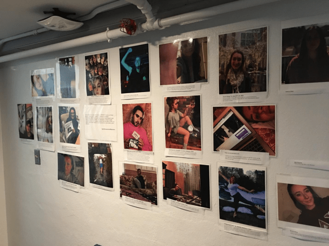 This image shows a gallery wall covered with approximately two-dozen selfies.