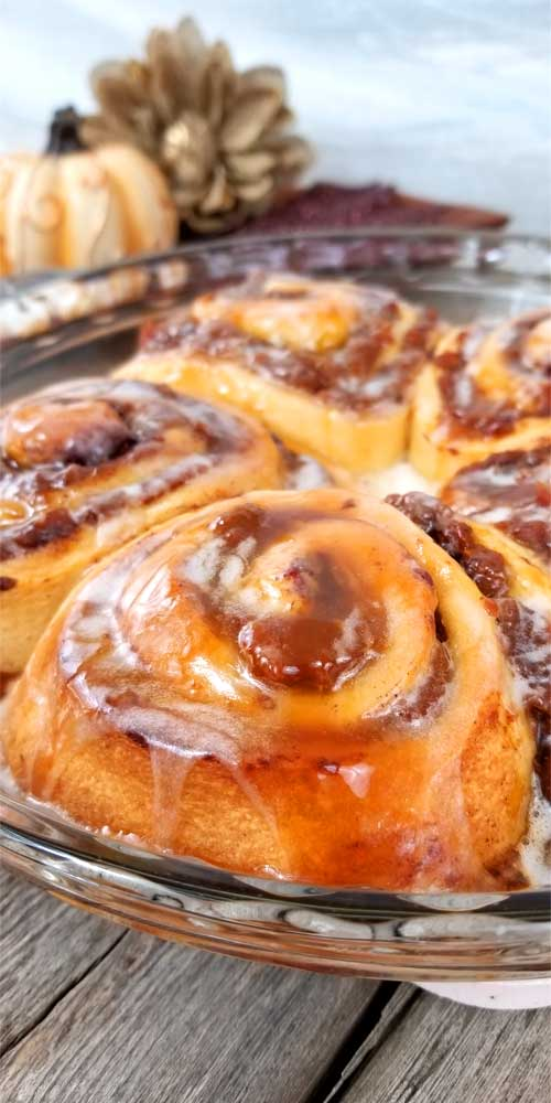 These Super Easy Pumpkin Butter Cinnamon Rolls are toasty warm, fresh from the oven. They are so delicious, extra rich, and gooey with spiced pumpkin butter and melty cream cheese frosting and a little caramel drizzle to top it all off with.