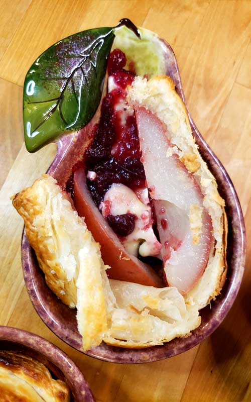 Impress your guests with a beautiful puff pastry dressed pear nestled in with warm brie and cranberry sauce. These Pastry Wrapped Pears with Cranberries and Brie are a delicious easy dessert anyone can make and it only takes a few minutes!