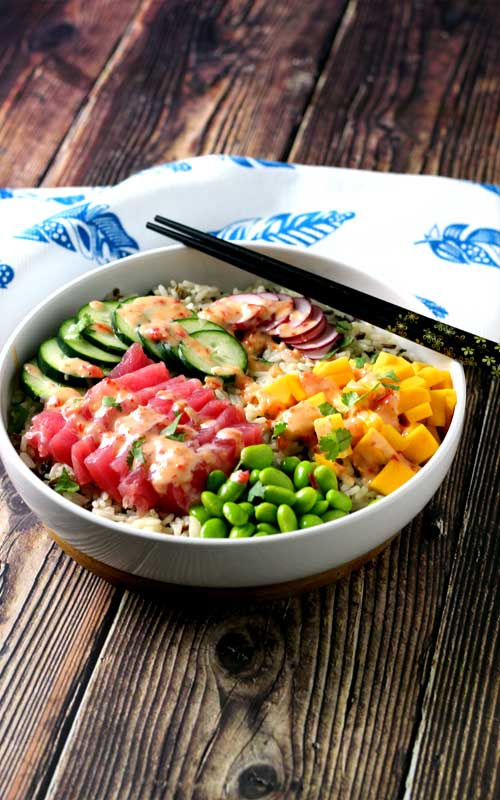 An absolutely divine Hawaiian Tuna Poke Bowl with fresh ahi tuna, bright crisp radish, cucumber, edamame, and sweet mango over wild rice with a drizzle of sweet chili aioli? Yes, please!