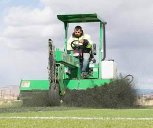 John Byrne/Tribune A FieldTurf employee steers a machine to scrape the artificial turf on one of the multi-purpose fields at Golden Eagle Regional Park on Monday.