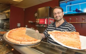 John Byrne/Tribune - Paul Erikson, owner of True New York Pizza Co. in Sparks, displays one of the many pizza's offered at his restaurant on Vista Boulevard.