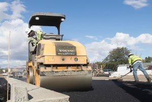 John Byrne/Tribune -  Road crews pour and level asphalt Friday morning at the corner of Pyramid and McCarran Boulevard in Sparks.