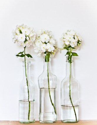 Three different bottles with the same flowers create a shabby chick hipster vibe