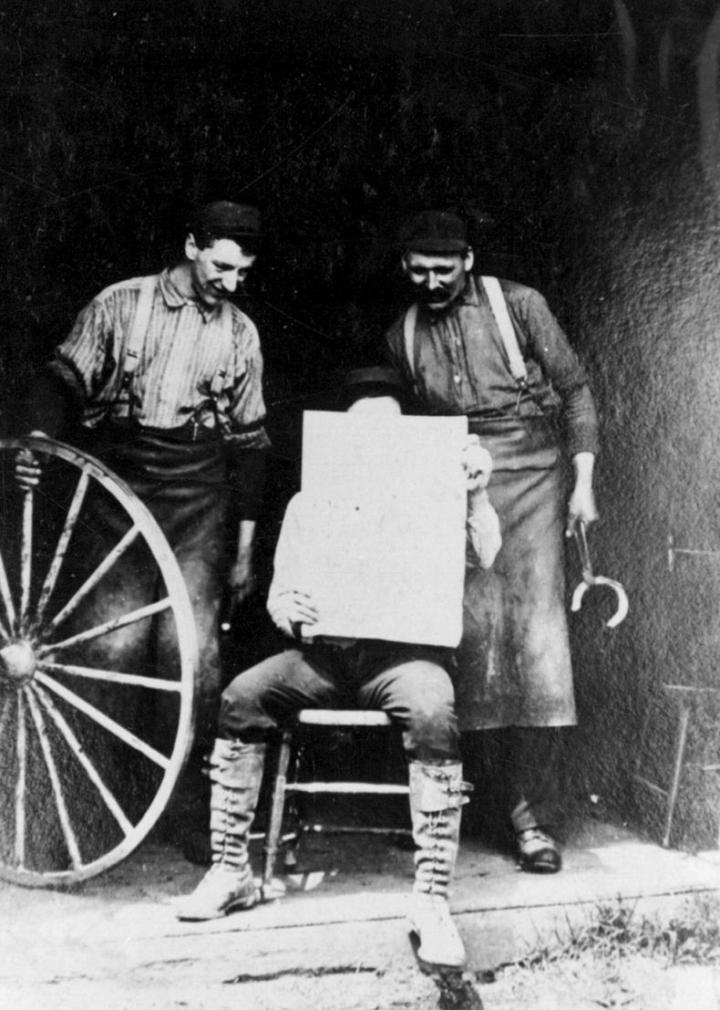 On the right is Frank Herbst.  The man behind the newspaper is Mr. Bennett.  The other is unknown